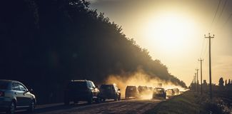 Cars drive into sunset with dust rising on countryside road, panoramic photo. Toned royalty free stock photography