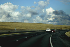 Cars driving. On the highway toward a storm royalty free stock images
