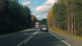 Cars driving on an asphalt road in the autumn forest stock video