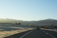 Country highway with cars leading towards mountains at sunrise. Cars driving down a country highway in the early morning as the sun rises casting a warm glow Stock Image