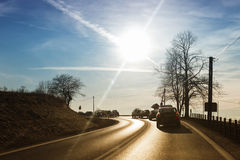 Cars driving down country road Royalty Free Stock Image