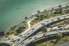 Cars driving on highway near ocean coast - city traffic aerial Royalty Free Stock Image