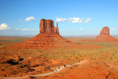 Cars Driving Through Monument Valley, Arizona. Left and Right Mittens in Monument Valley, Arizona dwarf the vehicles in the foreground Royalty Free Stock Images
