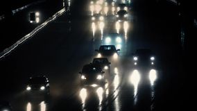 Cars Driving At Night In Rainstorm. Many cars passing in the rain with their lights reflecting on the wet road stock video footage