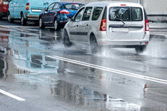 Cars driving through rain puddles on the road during rush hour Stock Photography