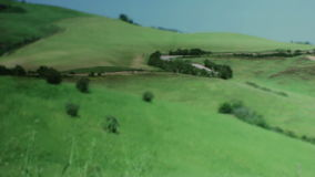 Cars Driving on a Road through Tuscany Italy. Medium wide shallow depth of field panning tracking slider shot of cars driving over a road through the green stock footage