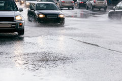 Cars driving on road with water puddles during heavy rain Royalty Free Stock Image