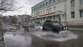 Cars driving on street road over muddy puddle and splashing water from wheels. PETROPAVLOVSK KAMCHATSKY CITY, KAMCHATKA PENINSULA, RUSSIAN FAR EAST - 12 MAY stock video