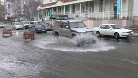 Cars driving on street road over muddy puddle and splashing water from wheels. PETROPAVLOVSK KAMCHATSKY CITY, KAMCHATKA PENINSULA, RUSSIAN FAR EAST - 12 MAY stock footage