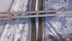 Cars driving on winter highway under suspension railway bridge drone view. Car traffic on snowy road on winter landscape. Aerial view train bridge over highway stock video