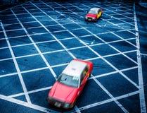 Cars driving through yellow no parking area on asphalt street Stock Photos
