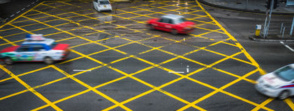 Cars driving through yellow no parking area on asphalt street Stock Image