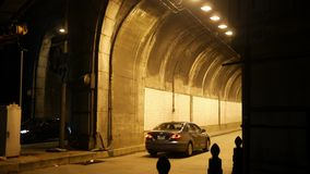 Cars entering urban tunnel at night near dark highway. 