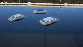 Cars in flooded water. Aerial view of three cars partially submerged in flooded water on road; Thailand Royalty Free Stock Photo