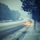 Cars in the fog. Bad winter weather and dangerous automobile traffic on the road. Light vehicles in fog. Winter Royalty Free Stock Photo