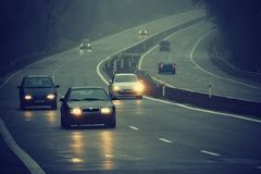 Cars in the fog. Bad winter weather and dangerous automobile traffic on the road. Light vehicles in foggy day royalty free stock photography