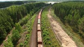 Cars of freight train passing to a distance at the double line railway in forests of Karelia, Russia. Aerial rear view Stock Photography