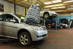 Cars in garage. Cars repair in the garage. Close-up of the car with open hood Stock Image
