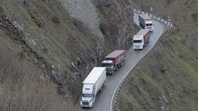 Cars go down a mountain road. Trucks drive over serpentine in Georgia. Traffic transportation. The cars go down a mountain road. Trucks drive over serpentine in stock video