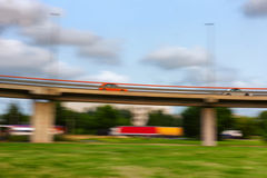 Cars go fast on a bridge on a summer day. Blurry Stock Photo