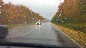 Cars go on the road asphalt. autumn beautiful view forest, raindrops on the glass car blurred background slow motion. Cars go on road asphalt. autumn beautiful stock video