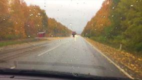 Cars go on the road asphalt. autumn beautiful view forest, raindrops on the glass car blurred travel background slow. Cars go on road asphalt. autumn beautiful stock footage