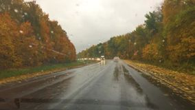 Cars go on the road asphalt. autumn beautiful view forest, raindrops on the glass travel car blurred background slow. Cars go on road asphalt. autumn beautiful stock footage