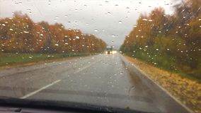 Cars go on the road asphalt. autumn travel beautiful view forest, raindrops on the glass car blurred background drive. Cars go on the road asphalt. autumn travel stock video