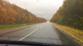 Cars go on the road asphalt. autumn travel beautiful view forest, raindrops on the glass car blurred background slow. Cars go on the road asphalt. autumn travel stock footage