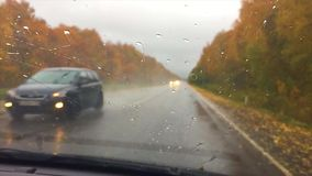 Cars go on the road asphalt. Autumn travel beautiful view forest, raindrops on the glass car blurred drive background. Cars go on the road asphalt. Autumn travel stock video