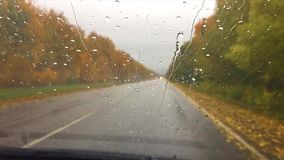 Cars go on the road asphalt. autumn travel beautiful view forest, raindrops on the glass car drive blurred background. Cars go on the road asphalt. autumn travel stock video