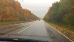 Cars go on the road asphalt. autumn travel beautiful view forest, raindrops on the glass drive car blurred background. Cars go on the road asphalt. autumn travel stock video footage