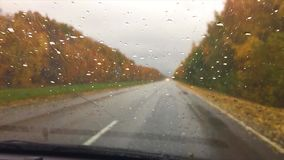 Cars go on the road asphalt. travel autumn beautiful view forest, raindrops on the glass car blurred background slow. Cars go on the road asphalt. travel autumn stock footage