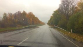 Cars go on the road travel asphalt. autumn beautiful view forest, raindrops on the glass car blurred background slow. Cars go on the road travel asphalt. autumn stock video footage