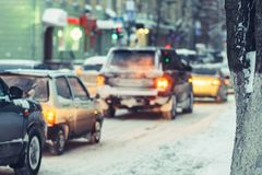 Cars go on a snowy road in the evening Royalty Free Stock Photos