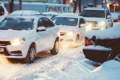 Cars go on a snowy road in the evening Stock Images