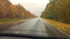 Cars go on travel the road asphalt. autumn beautiful view forest, raindrops on the glass car blurred background slow. Cars go on travel the road asphalt. autumn stock footage