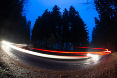 Cars going fast through a curve on a forest road. At dusk, on a rainy day - i.e. Potentially dangerous driving conditions Stock Photo