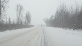 Cars going slippery rural road winter snow snowstorm falling. Cars going on slippery rural road in winter and snow snowstorm falling stock video footage