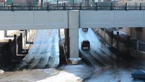 Cars going under underpass. Cars pass under a bridge followed by a flock of pigeons stock video