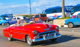 Cars of Havana, Cuba. Havana, Cuba - December 19, 2016: Tourists sightseeing in retro cars on Malecon, major avenue in Havana, Cuba Royalty Free Stock Photo