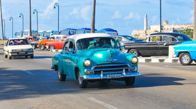 Cars of Havana, Cuba. Havana, Cuba - December 19, 2016: Tourists sightseeing in retro cars on Malecon, major avenue in Havana, Cuba Stock Photo
