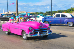 Cars of Havana, Cuba. Havana, Cuba - December 19, 2016: Tourists sightseeing in retro cars on Malecon, major avenue in Havana, Cuba Royalty Free Stock Photos
