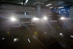 Cars with headlight in car wash. Black and white same vehicles illuminating sprayed water with headlights in car wash station Stock Photos