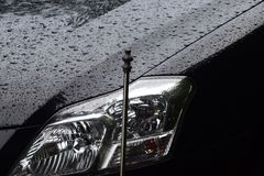 Cars Headlight with Front Body Parts Photograph. A black cars front headlight with rain water drops outside background photograph Stock Photography
