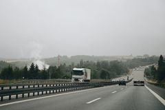 Cars on highway in foggy weather. Asphalt highway with cars on the road in foggy weather stock images