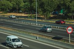 Cars on highway with heavy traffic and SPEED LIMIT sign in Madrid. Cars passing through multi lane highway with heavy traffic and SPEED LIMIT signpost, on sunset royalty free stock photo