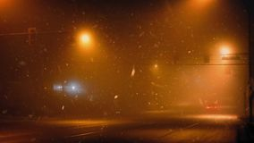 Cars On Highway At Night In Snowy Weather. Couple of cars driving on city road under flashing traffic lights in snowstorm stock footage