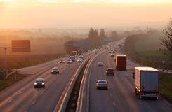 Cars on highway road at sunset Stock Photos