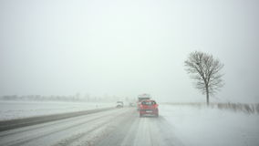 Cars on highway by snowstorm Royalty Free Stock Image